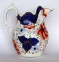 'Drape' patterned jug showing lustre appearing as copper when painted on blue and pink when painted on white.